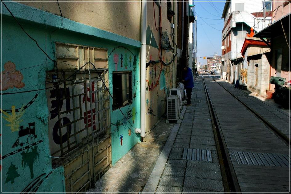 기찻길 옆에 아기자기한 그림이 그려진 건물들